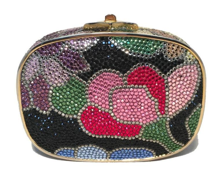 Beautiful Judith Leiber black floral box minaudiere in excellent condition.  Multicolor swarovski crystal exterior in a floral design over a black background.  Top button closure opens to a gold leather lined interior that holds an attached hidden