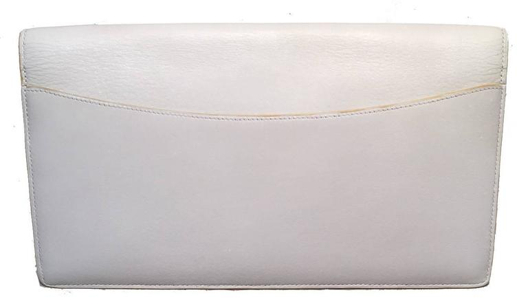 Beautiful vintage Hermes clutch in very good condition.  White box calf leather exterior with signature H logo along front flap and back side exterior slit pocket.  Front snap closure opens to a matching white leather lined interior that holds 2