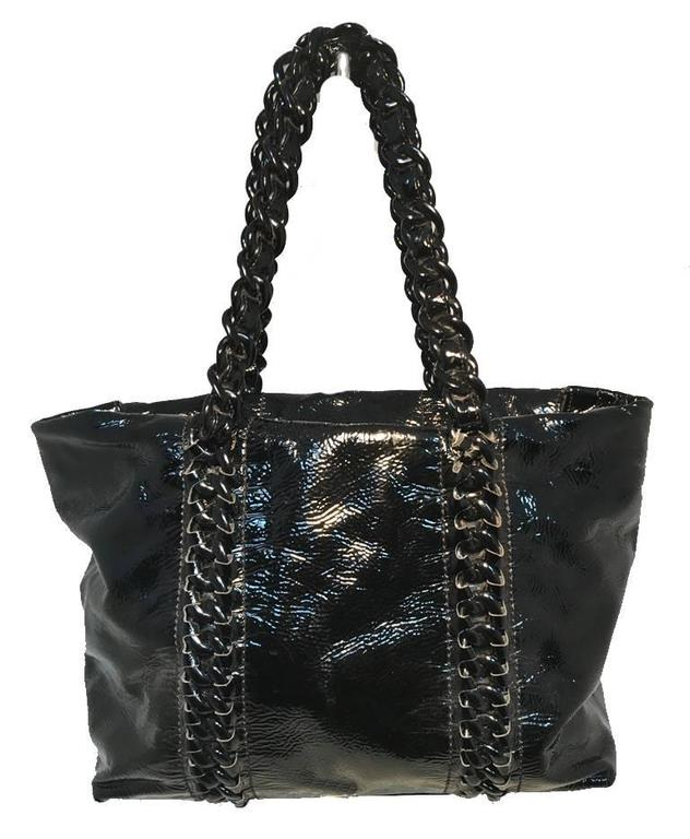 RARE Chanel black patent leather shoulder bag tote in very good condition. Black distressed patent leather exterior trimmed with silver hardware and black acrylic woven chain and leather straps that continue down both front and back sides of this