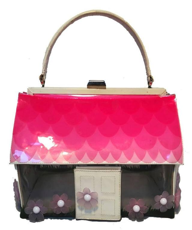 RARE & AMAZING Vintage Moschino House handbag in very good vintage condition.  White patent leather house with Clear walls and pink and purple flowers around base.  Pink scalloped roof, and silver hardware trim.  Door opens to reveal a mirror.  Top