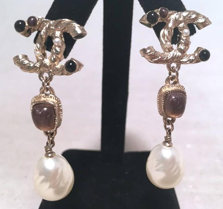 RARE CHANEL Silver dangle earrings in excellent condition.  Silver CC logo trimmed with onyx and amethyst tiny gemstones.  Next tier down features purple amethyst stones set in silver hardware and ends with genuine teardrop 1/2