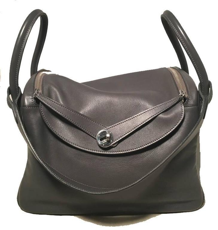 BEAUTIFUL Hermes grey leather lindy bag in very good condition.  Grey swift leather exterior trimmed with silver palladium hardware.  Double handles and attached shoulder strap for a variety of ways to wear.  Top twist double strap and zipper