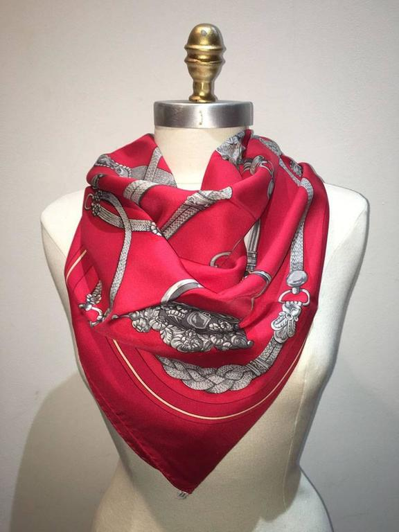 Beautiful Vintage Hermes red silk Gaucho scarf in very good condition.  Original silk screen design c1978 by Caty Latham features various horse dressings and bridal hardware over a red background.  100% silk, hand rolled hem, made in france.