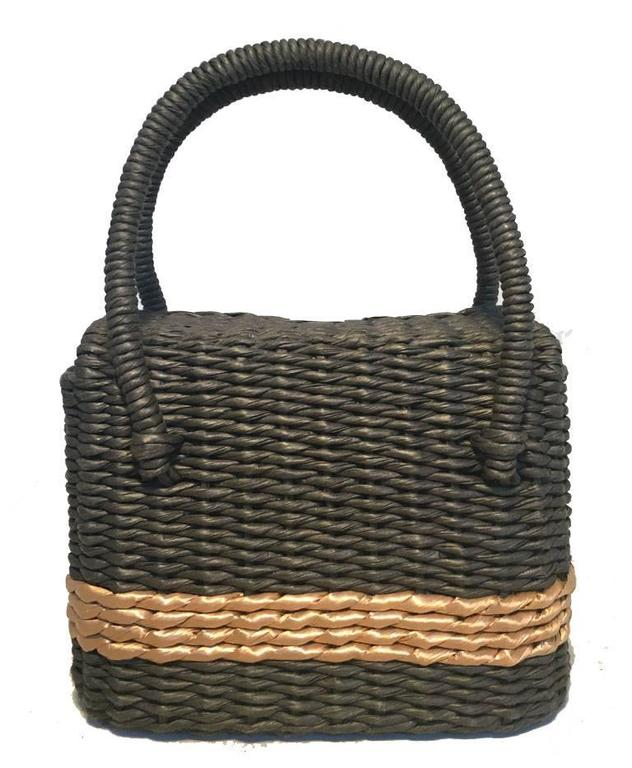 Limited Edition Chanel charcoal wicker basket bag in excellent condition.  Woven charcoal grey rattan wicker exterior with a tan stripe surrounding.  2 corded wicker handles and matte silver hardware closure.  Pinch latch closure opens via Double