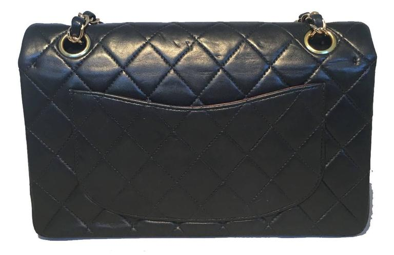 TIMELESS Chanel black 9inch 2.55 double flap classic in very good condition.  Quilted lambskin leather exterior trimmed with gold hardware and a woven chain and leather shoulder strap.  Front CC logo twist closure opens via double flap to a maroon