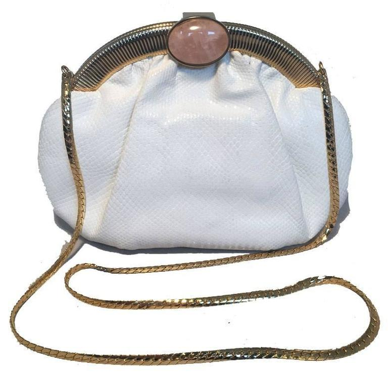 BEAUTIFUL Vintage Judith Leiber white lizard clutch in very good condition.  White lizard leather exterior trimmed with gold hardware and rose quartz stone along top closure.  Lifting closure opens to a tan nylon lined interior that holds 2 slit