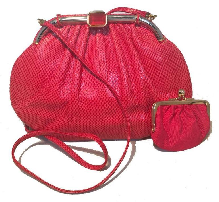 GORGEOUS Judith Leiber red lizard leather clutch in excellent vintage condition.  Red lizard leather exterior trimmed with gold hardware and a red centered glass stone along top closure.  Red nylon lined interior with 2 slit pockets and attached