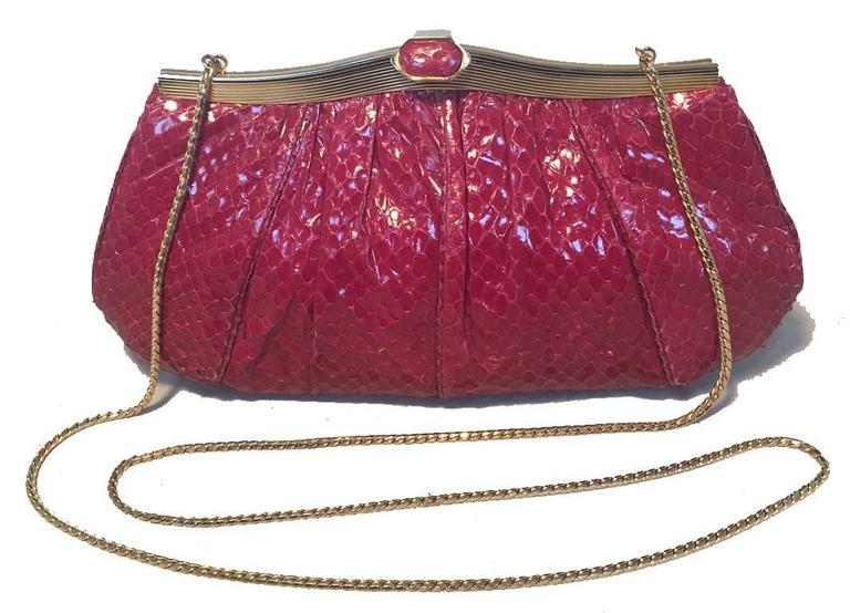 BEAUTIFUL Judith Leiber Maroon snakeskin clutch in very good vintage condition.  Maroon snakeskin exterior trimmed with gold hardware.  Top lifting closure opens to a burgundy satin lined interior that holds 1 side zippered pocket and attached gold