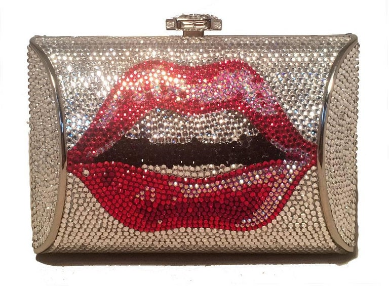 STUNNING NWT Judith Leiber Lip print crystal minaudiere in excellent condition. Silver crystal exterior with red lip print design on both sides. Top button closure opens to a silver leather lined interior that holds an attached hidden chain and