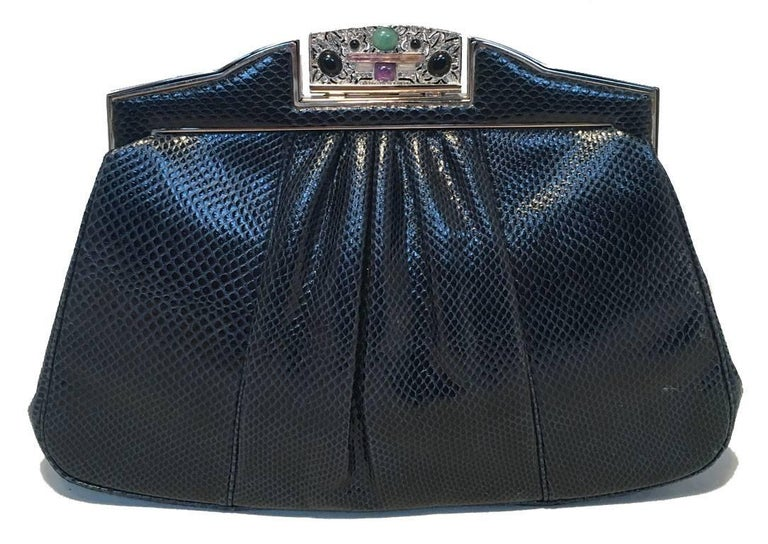 BEAUTIFUL vintage Judith Leiber navy blue lizard leather clutch in excellent vintage condition.  Navy blue lizard leather exterior trimmed with silver hardware.  top lifting closure opens to a black silk lined interior that holds 1 slit and 1