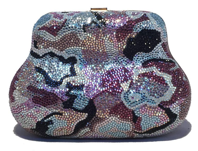 Beautiful Judith Leiber multicolor Swarovski crystal evening bag minaudiere in excellent condition. Swarovski crystal exterior with delicate blue, grey, purple, black and peach crystals in an abstract design throughout the exterior. Top button