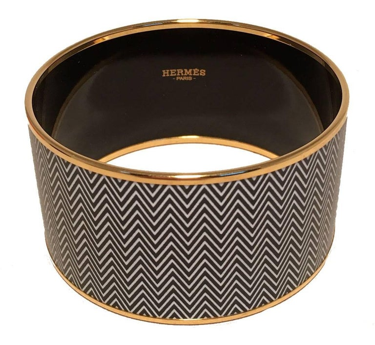 gorgeous Hermes zig zag enamel bangle bracelet in excellent condition.  Black and white zig zag enamel print trimmed with gold hardware.  No scuffs or major scratches.  Made in France stamped P.  Original bracelet box and duster included.