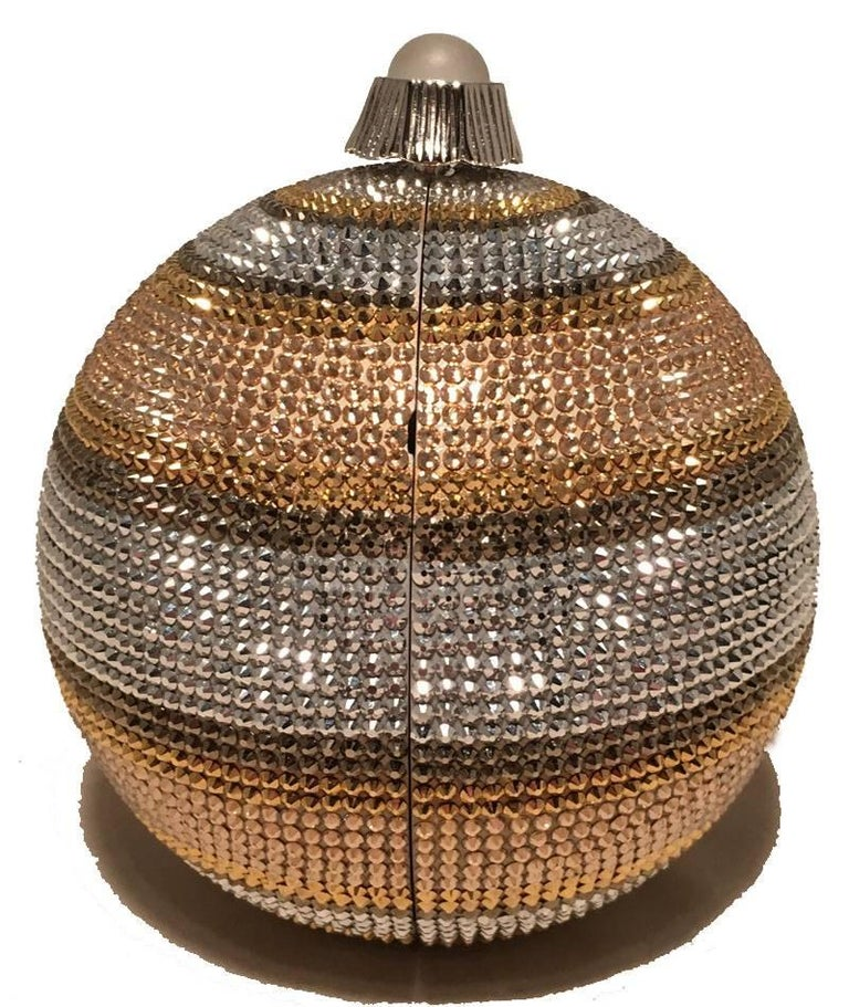 Beautiful Judith Leiber Swarovski Crystal Stripe Ball Minaudiere Evening Bag in excellent condition.  Striped gold, silver, and bronze swarovski crystal exterior trimmed with silver hardware and a top button closure.  Silver leather interior holds a