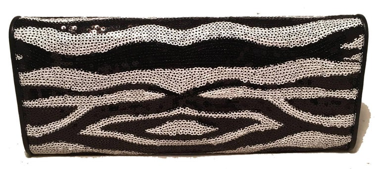 Beautiful Judith Leiber Zebra Stripe Sequin Clutch in excellent condition.  Black and White zebra stripe sequin pattern exterior trimmed with black leather, silver hardware and a front twist lock large stone closure.  purple silk lined interior with