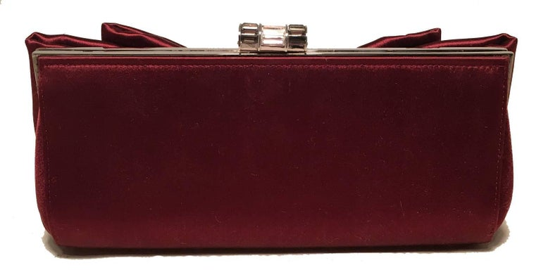 GORGEOUS Judith Leiber Dark Red Silk Satin Bow Front Clutch Evening Bag in excellent condition.  Dark red silk exterior with bow front detail and silver hardware.  Top lift crystal closure opens to a purple silk lined interior that holds 1 side slit