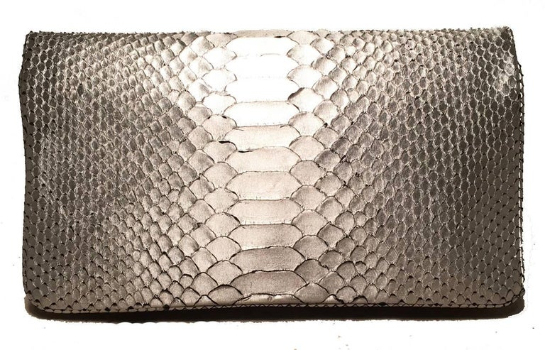 stunning Judith Leiber Silver Faux Snakeskin Python Clutch in excellent condition.  Silver faux snakeskin python exterior trimmed with silver hardware in a unique cage pattern along the front flap.  Single flap snap style closure opens to a purple