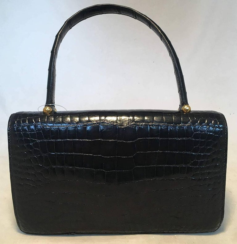RARE Vintage Hermes black alligator handbag in excellent condition.  Black alligator exterior trimmed with a gold spring latch closure. Single flap style closure opens to a black soft leather lined interior that holds 3 slit, 1 lipstick, and 1