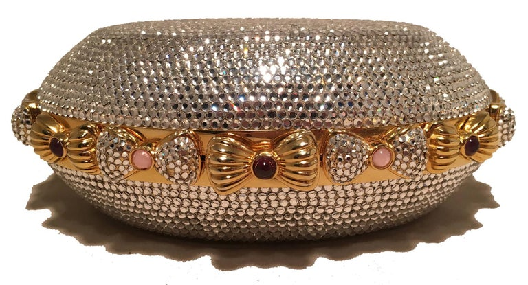 BEAUTIFUL Judith Leiber Swarovski Crystal Oval Bow Trim Minaudiere Evening Bag Clutch in excellent condition. Clear Swarovski crystal exterior in an oval shape surrounded by crystal bows around the outside. Each bow features a delicate small colored