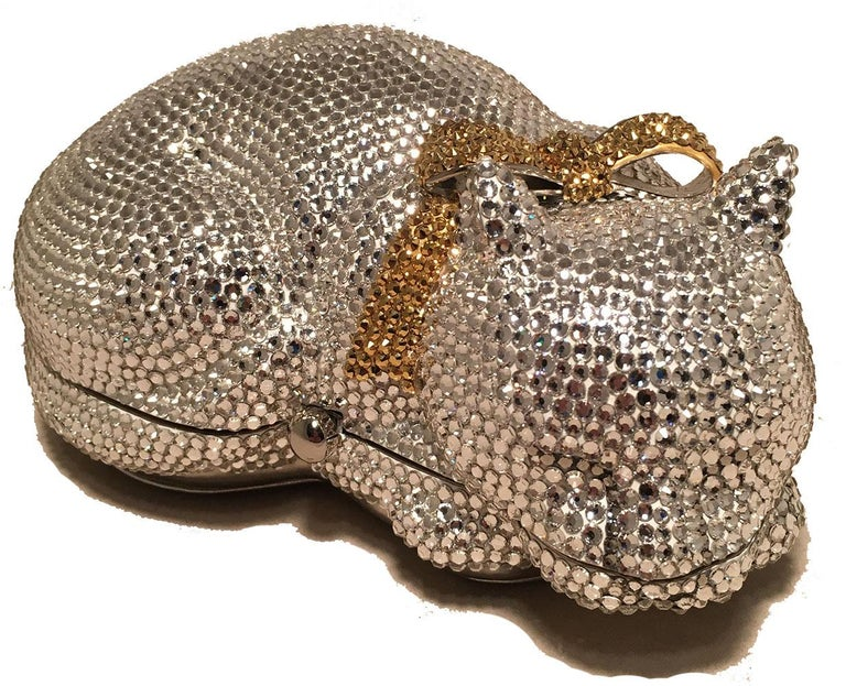 ADORABLE Vintage Judith Leiber cat minaudiere in excellent condition. Clear Swarovski crystal body with a gold crystal bow tie at neck. Silver leather exterior base. Button closure opens to a silver leather lined interior. Excellent condition, no