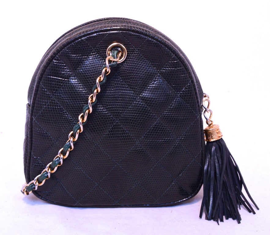 FABULOUS CHANEL dark green lizard pouchette wristlet in excellent condition.  Dark green lizard leather exterior trimmed with woven chain and leather handle and leather fringe tassel zip pull detail.  Top zipper closure opens to a black leather