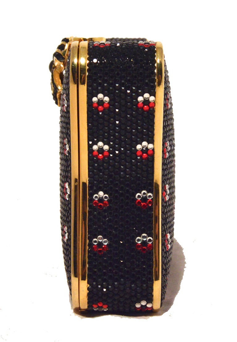 GORGEOUS JUDITH LEIBER Swarovski crystal floral box minaudiere in excellent condition.  Black swarovski crystal exterior with gold hardware trim and a delicate red and white crystal flower print surrounding the outside.  Top pearl push button