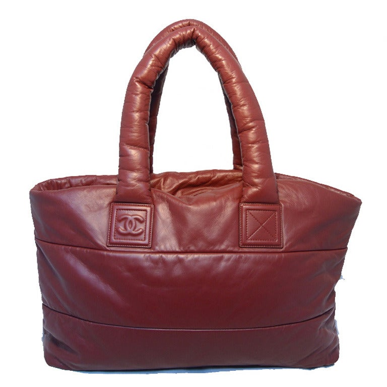 FABULOUS CHANEL burgundy leather cocoon tote in excellent condition.  Puffy burgundy quilted leather exterior with two comfortable leather shoulder strap handles.  Top double zipper closure opens to a black quilted leather lined interior that holds
