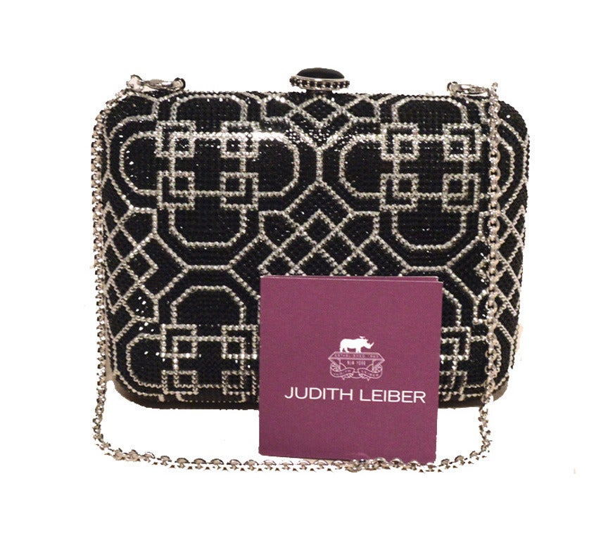 Fabulous Judith Leiber Swarovski crystal art deco style minaudiere clutch in excellent NWT condition.  Black and silver Swarovski crystal exterior in a stunning art deco print pattern.  Top button closure opens to a silver leather lined interior