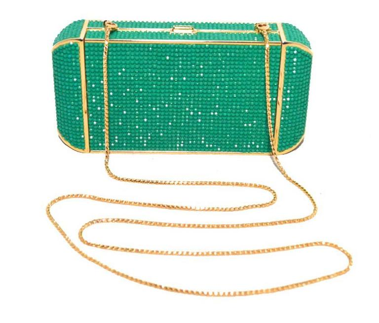 This beautiful Judith Leiber piece is in excellent condition.  The exterior features stunning green and blue Swarovski crystals trimmed with gold hardware.  The push button closure opens to an immaculate gold leather interior that holds a removable