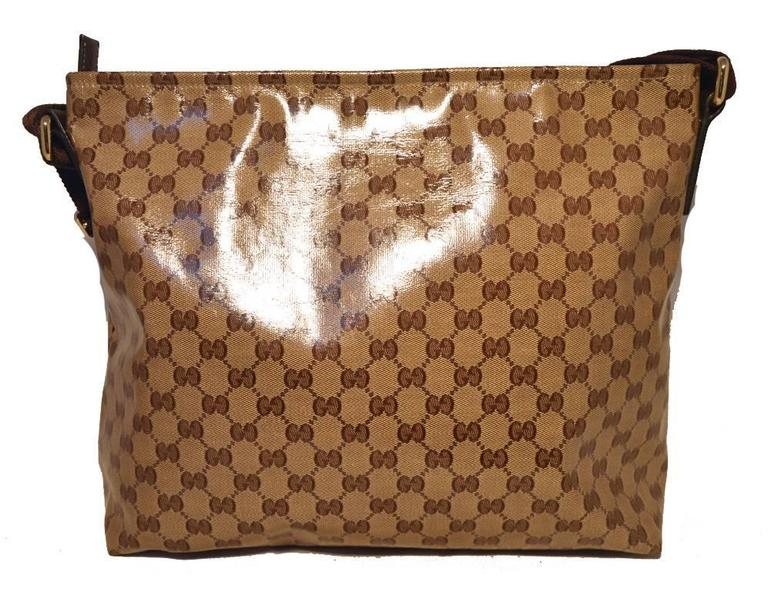 Stunning GUCCI monogram shoulder bag in excellent condition.  Coated monogram canvas exterior trimmed with a woven brown adjustable shoulder strap.  Top zipper closure opens to a brown cotton lined interior that holds one side zippered pocket.  No