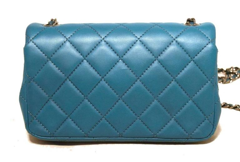 BEAUTIFUL Chanel teal extra mini classic flap in excellent condition.  Teal quilted lambskin leather exterior trimmed with shining silver hardware and signature woven chain and leather shoulder strap.  Front cc twist closure opens single flap style