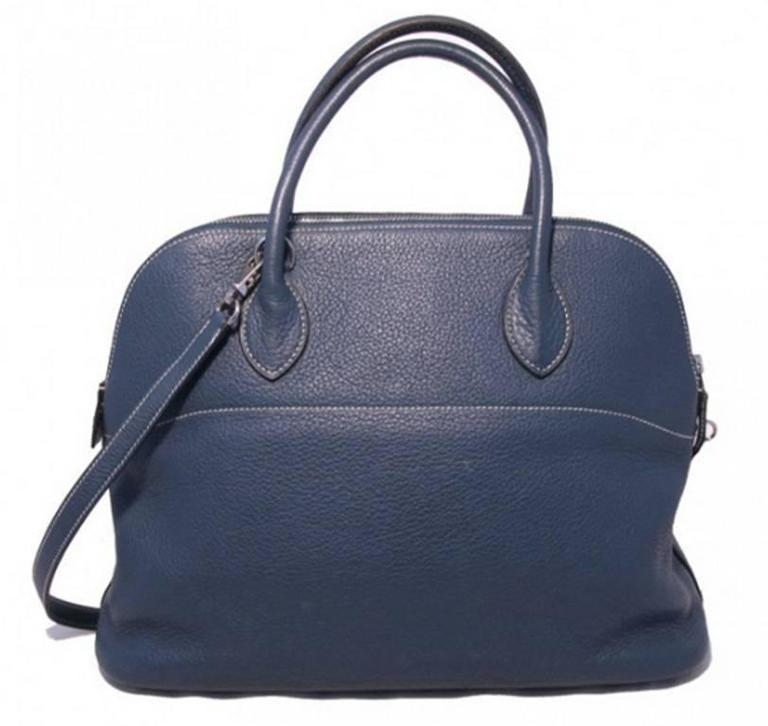RARE Hermes Blue Clemence leather Bolide in Very Good condition. Exterior features blue clemence leather trimmed with palladium hardware and comes complete with a removable matching leather shoulder strap to easily convert this piece from hand to