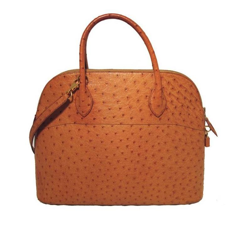 Authentic Hermes ostrich bolide bag in very good condition. Exterior features stunning tan ostrich leather and is perfectly trimmed with gold hardware. The top zipper closure opens to a tan lambskin interior that holds 1 side slit pocket. There are