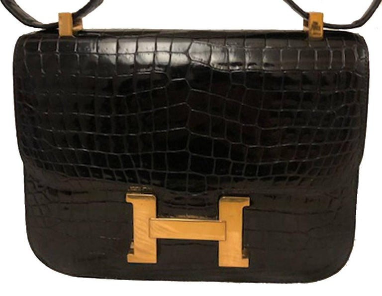 AUTHENTIC HERMES black crocodile constance bag in excellent vintage condition. Black crocodile leather exterior trimmed with shining gold hardware. Lift latch single flap style closure opens to a black leather lined interior that holds 2 slit and 1