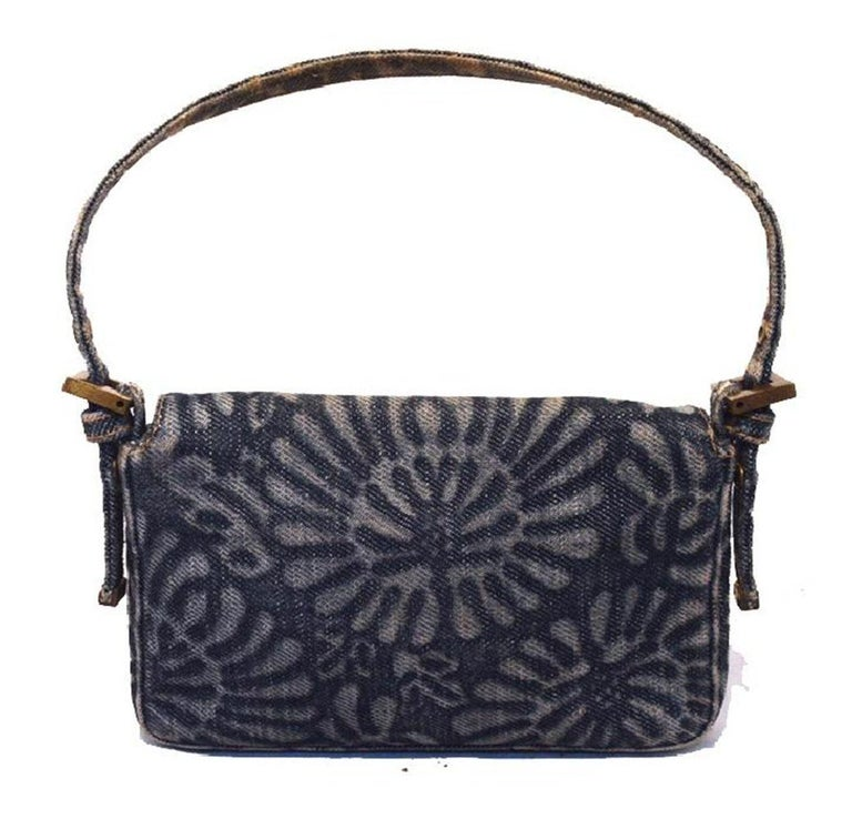 Fendi denim floral mini baguette in excellent condition. Denim exterior trimmed with bronze hardware. Signature Fendi buckle closure opens single flap style to a navy blue woven nylon interior that holds 1 small side pocket. this piece is in