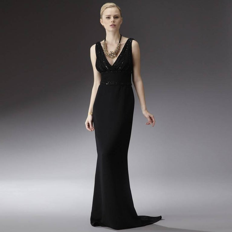 Badgley Mischka Gown Brand New with Tags Bead Trim on Bodice and around waist Zipper and Hook Closure Pleated Bodice V-Shaped Front and Back Top We are happy to provide measurements upon request Shell: 97% Polyester 3% Spandex Lining: 100% Polyester