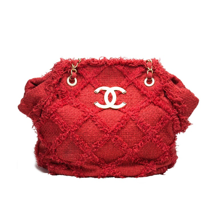 Red soft woven tweed Chanel tote with flat bottom and large CC logo  Year: 2009 Antique gold hardware Four bottom feet Flat bottom Tweed interwoven chain Diamond stitched woven detail pattern Large CC antique gold logo Beige canvas lined
