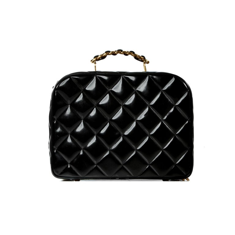 Chanel Vintage Black Quilted Patent Vanity Shoulder Bag   1991 {VINTAGE 26 Years} Gold hardware Classic Interwoven top handle Detachable classic interwoven chain strap Patent leather diamond stitching Vanity style ideal for holding makeup or used as
