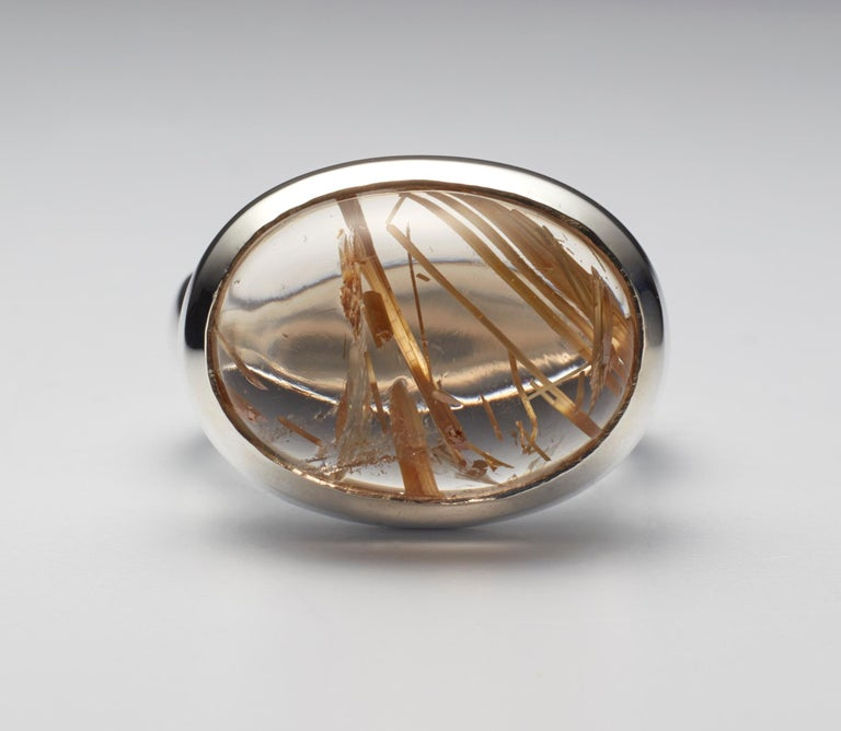 Golden Brazilian rutilated quartz cabochon silver ring. One of a kind, hand made by Christopher Phelan Fine Jewelry. Cabochon size 20 x 15 millimeter. Width of band 6 millimeter. Ring size 6 ¼ .