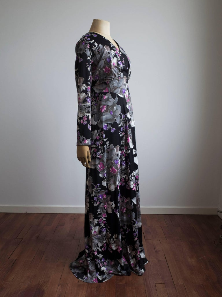 1960s Long sleeve gown by Maison Rigah, Amsterdam. Never been worn - still has original tags.  All over black, pink and purple floral print.  Features long ties to secure and accentuate the waist. Full back zip. Fully lined. Outer: 100%