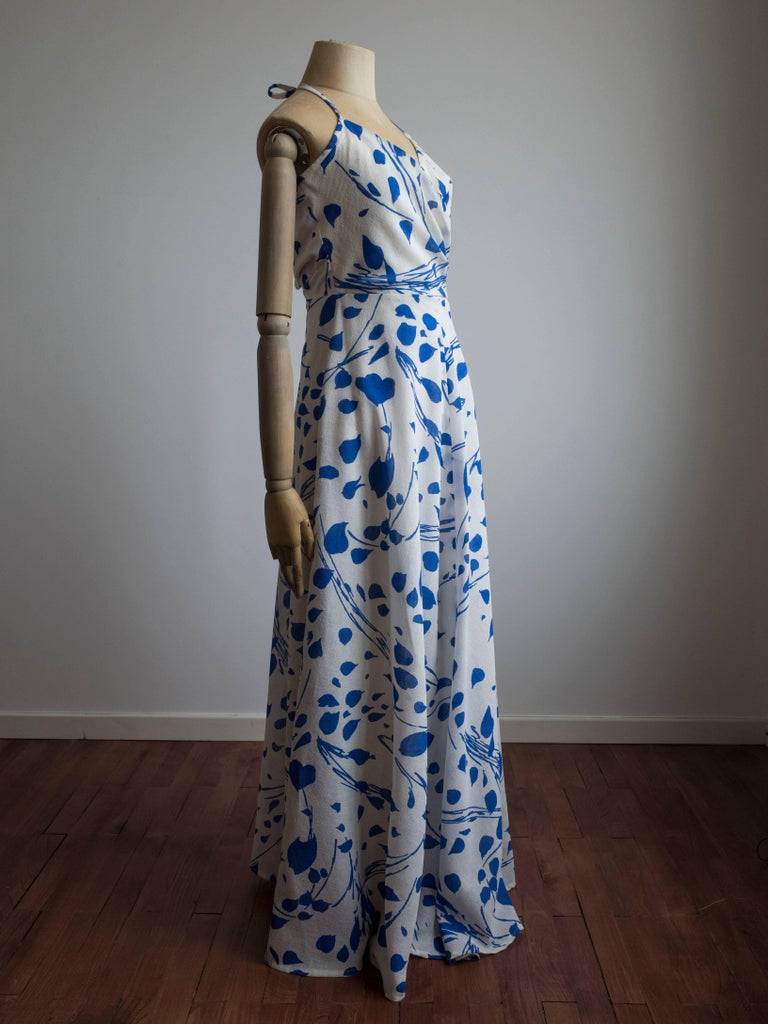 1960s blue and white floral print dress by Jean Allen. Made in London, England. Never been worn - still has original tags. Halter style neckline with cross-over bust and pleating at the waist. The full circle skirt is bias cut with beautiful