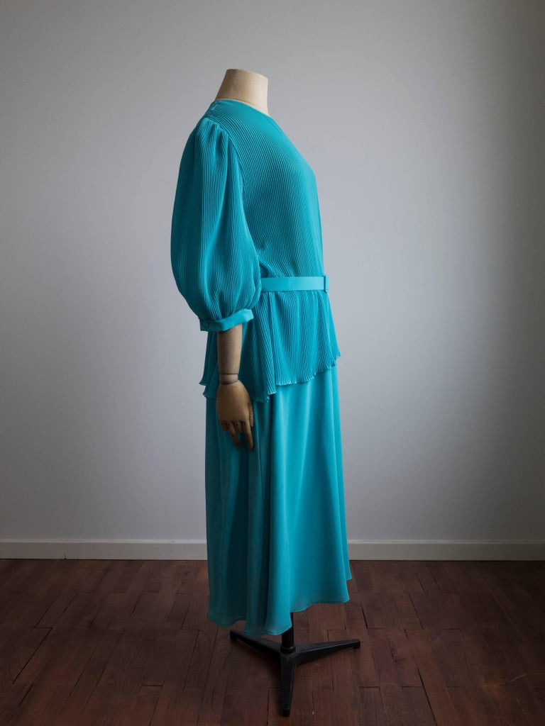Vintage 1980s evening dress by Hermann Lange Collection. Never been worn - still has original tags.  Pleated top featuring an asymmetrical peplum and belt with crystal accents. Full sleeves with volume at the shoulder. Keyhole at the back neck.