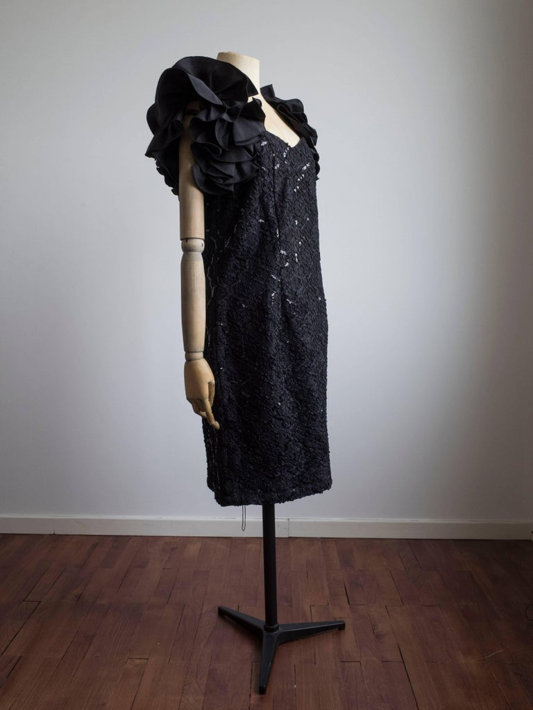 Beautiful black 1980s cocktail dress by Meico.  Never been worn - still has original tags. Features sweetheart neckline and full ruffle sleeves. The body of the dress is a textured cord and lace with black sequin for shimmer. Full back zip. Dress is