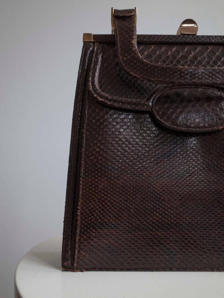 Vintage 1950s handbag in reptile skin leather is an exquisite piece of craftsmanship. Warm chocolate brown color with brass clasp and hardware. Two sturdy horseshoe handles.  The purse opens to a main leather compartment with a secondary pocket and