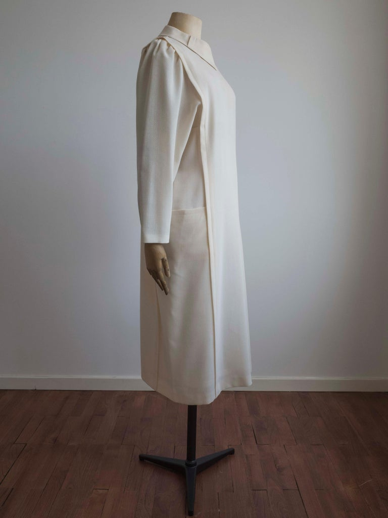 Vintage 1960s dress in a soft cream wool blend by Schworm Modell.  Features pleated dolman sleeves and side pockets. Fully lined with zipper at centre back. This dress has been professional cleaned.  Outer: 45% Wool, 55% Polyester Lining: 100%