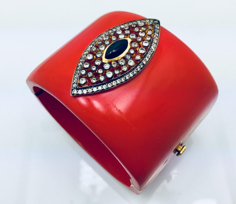 The red marquise cuff  is a cuff even wonder woman would be envious of. The bold piece includes a marquise cut black onyx stone surrounded by a cubic zircon. The bracelet is hinged and fastens with a push tab insert closure.   As featured in Vogue