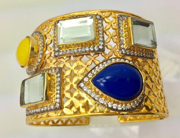 A gold lattice frame becomes a gleaming backdrop for the brightly colored blue and yellow teardrop stones, as well as three mirrored polki square stones. The statement cuff is an attention commanding finishing touch you will treasure, and is