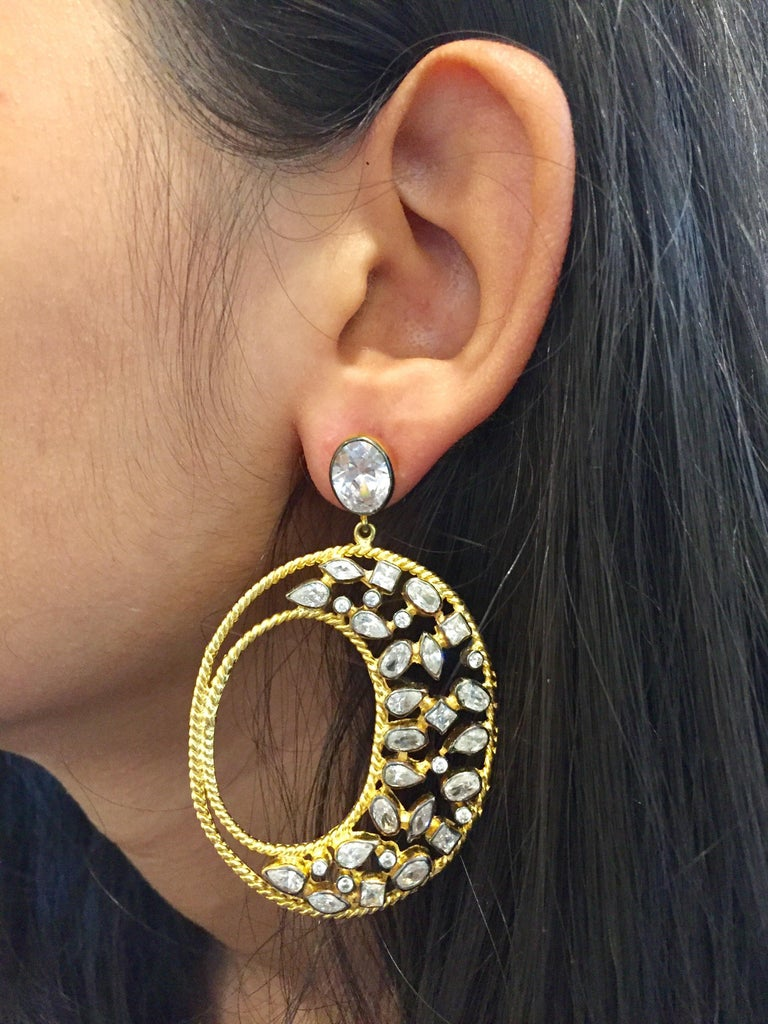 This gorgeous gold and CZ Diva hoop earrings are the ultimate in exotic glamor. With twisted gold wire forming the outline, the field of generously scattered CZ stones delivers unmatched sparkle. These large earrings are versatile enough to