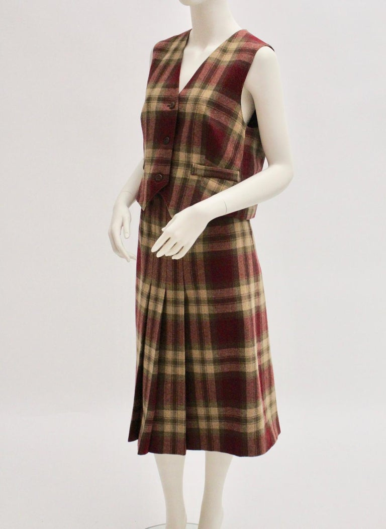 This Tartan Vintage set in the colors red and camel consists of a pleated skirt and a gilet. The skirt has 3 pleats at the frontside and at the backside. The skirt features a partly elastic waist - to set with a rubber band. Zip closure The gilet