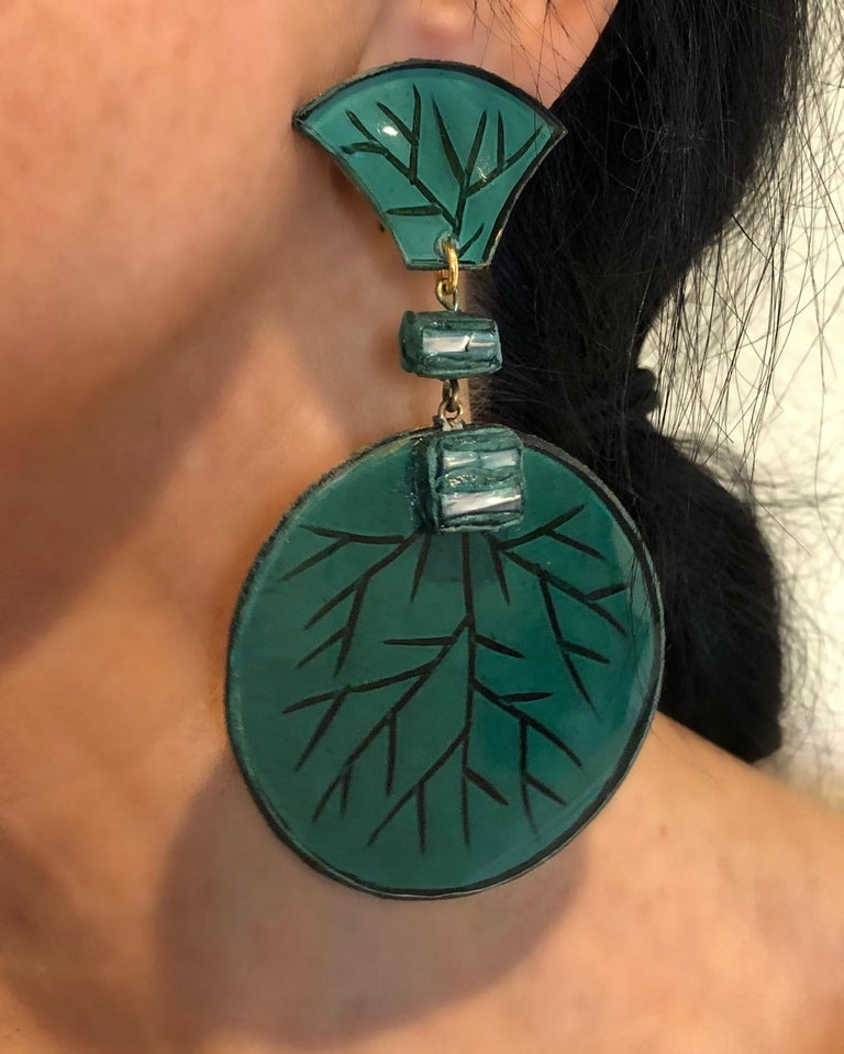 Light and easy to wear, these handmade artisanal circle clip-on earrings were made in Paris by Cilea. The earrings are comprised of green and gold enameline (resin and enamel composite) and depict three-dimensional pop art circles. Throughout the