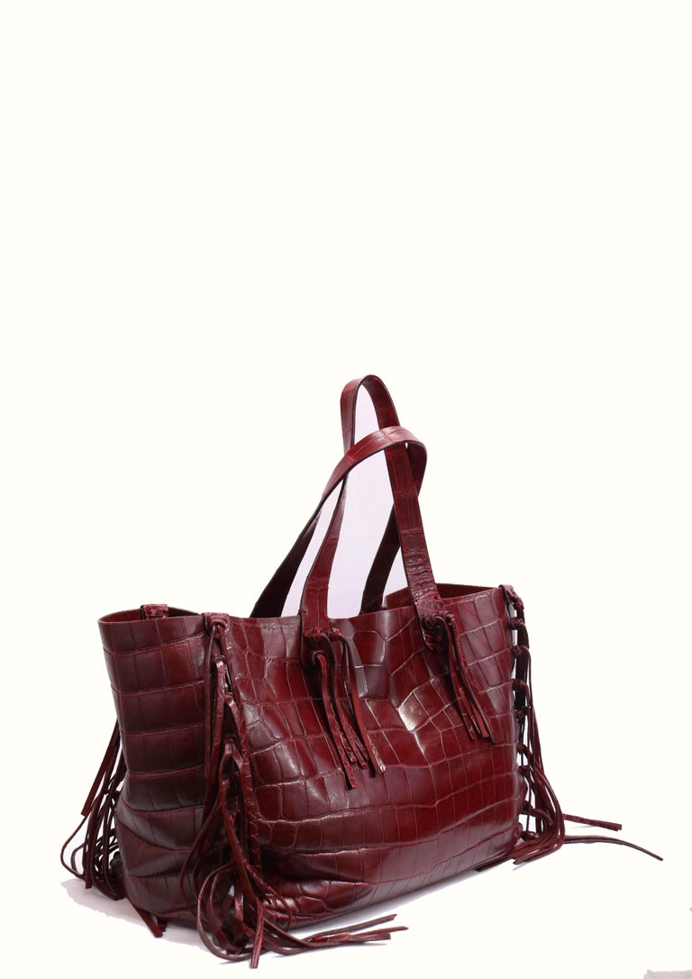 Crocodile leather tote bag in red with fringe trim, and open top.  -Suede interior with patch and zipper pockets  -Red wine tone  -Made in Italy.